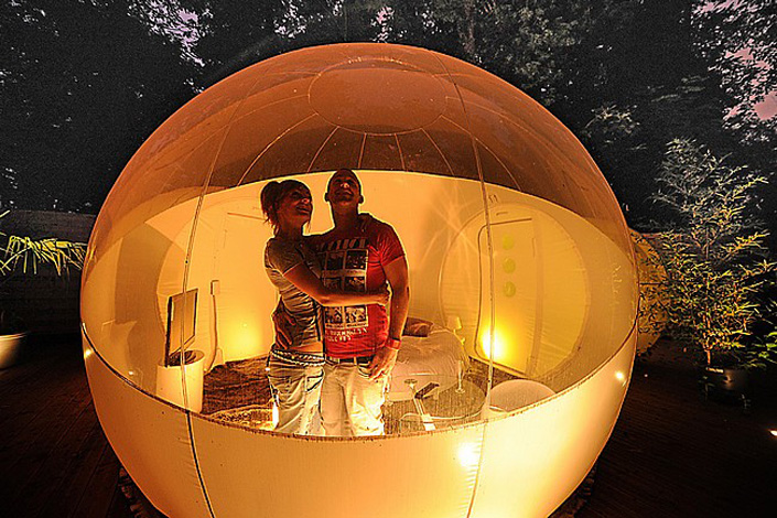 "TO GO WITH AFP STORY BY DELPHINE PAYSANT A couple visits a ""bubble room"" on July 26, 2011 in a parc of Roubaix, northern France. The bubble room made with recycled plastic and kept under pressure by a silent blower can be rent as an hotel room in the middle of the nature. AFP PHOTO / PHILIPPE HUGUEN"